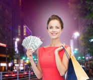 Smiling woman with shopping bags and money Stock Photo