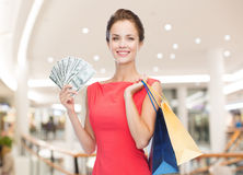 Smiling woman with shopping bags and money. Sale, money, people and holidays concept - smiling woman in red dress with shopping bags and dollars over mall Stock Photography