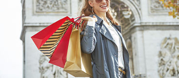 Smiling woman with shopping bags in Paris looking into distance. Stylish autumn in Paris. smiling elegant woman with shopping bags near Arc de Triomphe in Paris Stock Photography