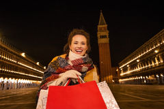 Smiling woman with shopping bags on Piazza San Marco in evening Royalty Free Stock Photos