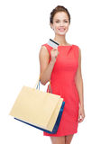 Smiling woman with shopping bags and plastic card Royalty Free Stock Photography