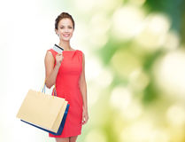Smiling woman with shopping bags and plastic card Royalty Free Stock Image