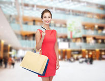 Smiling woman with shopping bags and plastic card Stock Photography