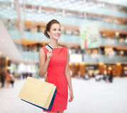 Smiling woman with shopping bags and plastic card Stock Photo