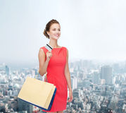 Smiling woman with shopping bags and plastic card Royalty Free Stock Images