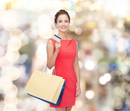 Smiling woman with shopping bags and plastic card Stock Images
