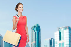 Smiling woman with shopping bags and plastic card Stock Image