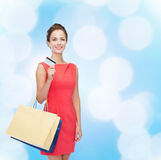 Smiling woman with shopping bags and plastic card Royalty Free Stock Photos