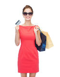 Smiling woman with shopping bags and plastic card Stock Photos