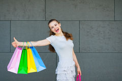 Smiling woman with shopping bags showing thumbs up Stock Image