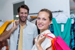 Smiling woman with shopping bags standing in front of her man Royalty Free Stock Photography