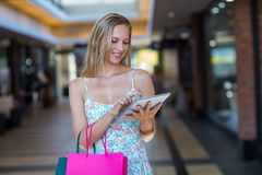 Smiling woman with shopping bags using tablet computer Royalty Free Stock Photography
