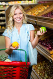 Smiling woman with shopping basket holding apples Stock Photo