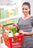 Smiling woman with shopping basket Royalty Free Stock Photos