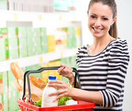 Smiling woman with shopping basket Royalty Free Stock Images
