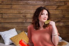 Smiling woman after shopping with colourful paper bags, banking. Happy smiling woman after shopping with colourful paper bags and banking credit card sits on bed royalty free stock image