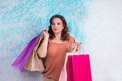 Smiling woman at shopping holding colourful paper bags, packages. Smiling woman at shopping holding colourful paper bags in both hands stock photos