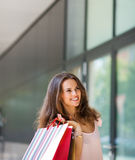 Smiling woman shopping, holding up colourful shopping bags Royalty Free Stock Photos
