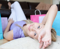 Smiling woman after shopping lying on the floor Royalty Free Stock Photos