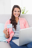 Smiling woman shopping online through laptop using credit card Stock Image