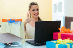 Smiling woman shopping online and showing ok at home Stock Image