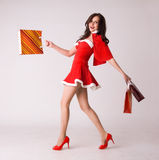 Smiling woman shopping in red xmas costume Royalty Free Stock Photos