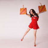 Smiling woman shopping in red xmas sexy costume Royalty Free Stock Images