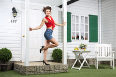 Smiling woman in shorts poses next to simple entrance door Royalty Free Stock Photography