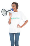 Smiling woman shouting in megaphone Stock Photo