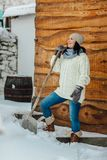 Smiling woman shoveling snow. A woman cleaning snow from her porch at a country house Royalty Free Stock Photos