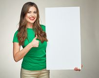 Smiling woman show thumb up with big sign board. Isolated portrait on gray background Royalty Free Stock Image