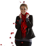 Smiling woman showered with rose petals. A smiling young beautiful woman isolated on a white background as heart shaped red rose petals fall to the ground and on Royalty Free Stock Photo