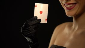Smiling woman showing ace of hearts into camera, isolated on black background. Stock footage stock video footage