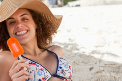 Smiling woman showing a beaming smile while holding an ice looly Stock Photo