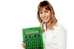 Smiling woman showing big calculator. Woman accountant holding big green calculator Royalty Free Stock Image