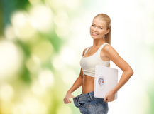 Smiling woman showing big pants and holding scales Stock Image
