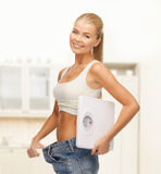 Smiling woman showing big pants and holding scales Stock Photography
