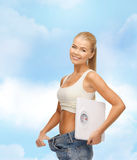 Smiling woman showing big pants and holding scales Stock Photo