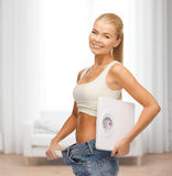 Smiling woman showing big pants and holding scales Royalty Free Stock Image