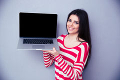 Smiling woman showing blank laptop display Stock Photo