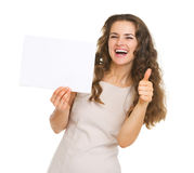 Smiling woman showing blank paper and thumbs up Stock Photos