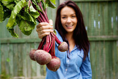 Smiling woman showing a bunch of beetroots Stock Images