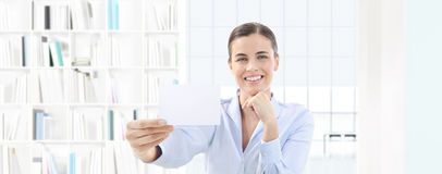 Smiling woman showing business card in her hand on interior offi Royalty Free Stock Photo
