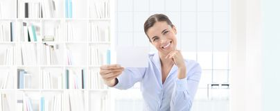 Smiling woman showing business card in her hand on interior offi Royalty Free Stock Images