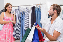 Smiling woman showing clothes to her man Royalty Free Stock Image