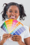 Smiling woman showing colour charts Stock Photos
