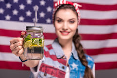 Smiling woman showing detox drink in hand with American flag on background Stock Image