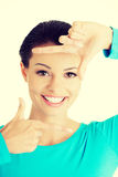 Smiling woman is showing frame by hands. Royalty Free Stock Photos