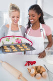 Smiling woman showing freshly baked cookies to friend Stock Photos
