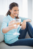 Smiling woman showing glass of white wine at camera Stock Images